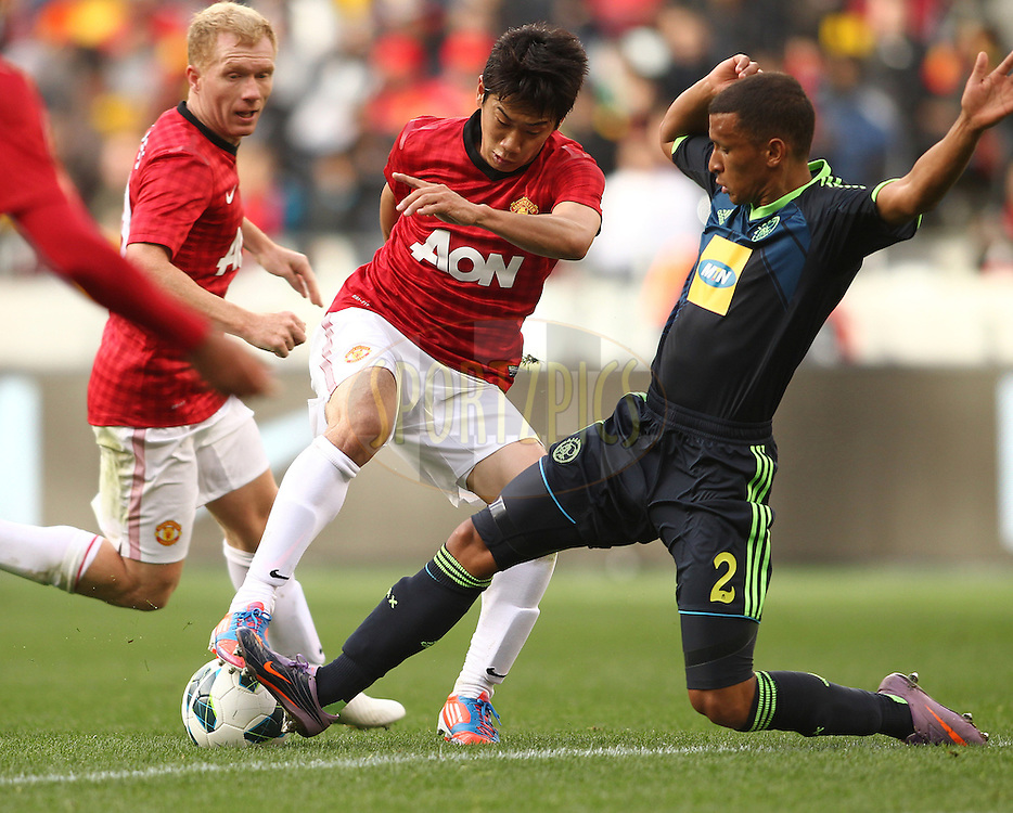 Shinji Kagawa of Manchester United attempts to get past Nazeer Allie of Ajax Cape Town tackle during the Football Invitational 2012 match between Ajax Cape Town and Manchester United held at Cape Town Stadium on 21 July 2012 in Cape Town, South Africa..Photo by Shaun Roy / Sportzpics