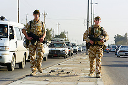 British soldiers from the Duke of Wellington's Regiment wearing desert camouflage, and body armor, carrying SA80 assault rifles which are fitted with SUSAT sights, Patrol through the streets of Basra city providing a security cordon for engineers who are doing a search for Improvised Explosive Devices also known as IED's  during Op-Telic in March 2005.