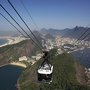 Cable cars taking tourists and sightseers to and from the top of Sugar Loaf Mountain, one of the iconic tourist destinations in Rio de Janeiro. Rio de Janeiro, Brazil. 27th August 2010. Photo Tim Clayton