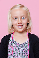 Portrait of a happy young girl over pink background