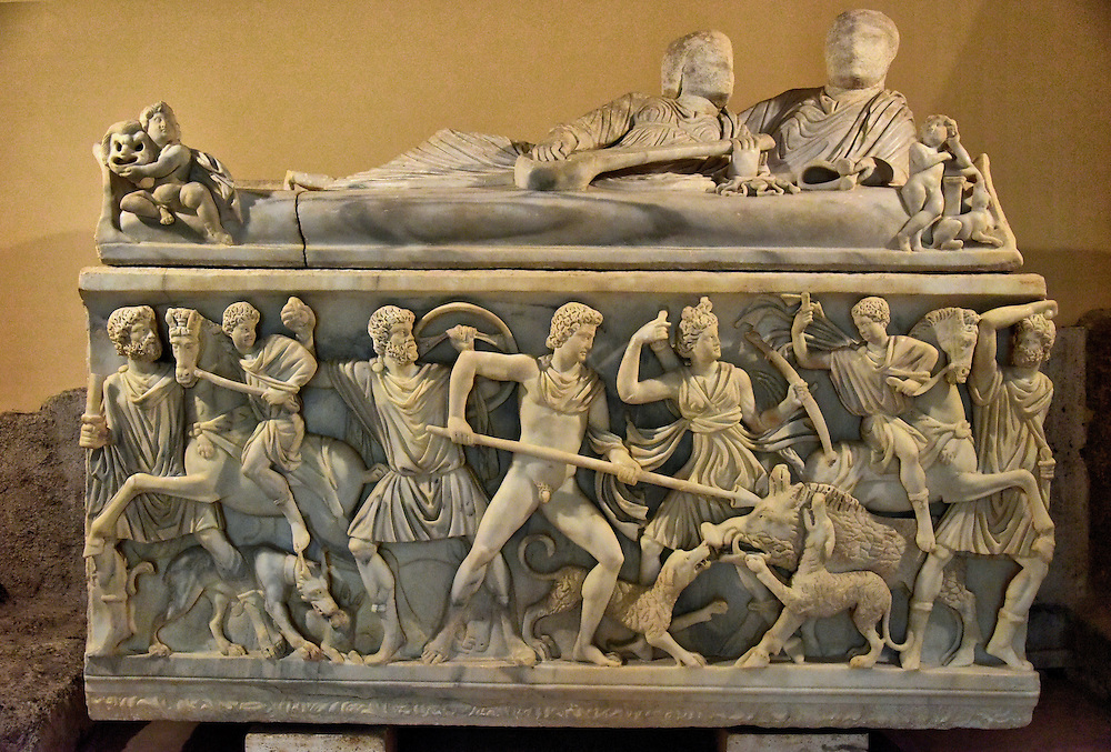Faceless Marble Sarcophagus at Capitoline Museums in Rome, Italy <br /> The Capitoline Museums display several sarcophagi.  This 15th century coffin from the Italian town of Vicovaro has the classic Calydonian Hunt scene carved into marble. The Calydonian Boar was a monster from Greek mythology.  It was tracked by numerous Greek heroes but it was Atalanta, a virgin huntress, whose arrow first pierced the beast. It was then speared by Meleager.  Notice the man and women laying side-by-side. The faces would be carved in when the sarcophagus was purchased.