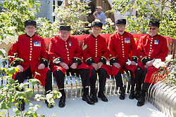 © Licensed to London News Pictures. 19/05/2014. London, England. Chelsea Pensioners relax on a specially designed bench in the London Square garden. Press Day at the RHS Chelsea Flower Show. On Tuesday, 20 May 2014 the flower show will open its doors to the public.  Photo credit: Bettina Strenske/LNP