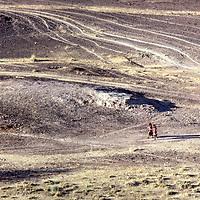 Two tiny female figures traverse barren desert landscape.