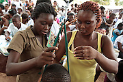 Ghana: 25 April 2012, A woman helps a nurse weigh her child at the Dodowa new town health outreach point in Dodowa.The GAVI Alliance is a public-private partnership that brings together developing country and donor governments, WHO, UNICEF, the World Bank, the vaccine industry in both industrialised and developing countries, research and technical agencies, civil society, the Bill & Melinda Gates Foundation and other private philanthropists.  Set up in 2000 as the Global Alliance for Vaccines and Immunisation, GAVI's mission is to save children's lives and protect people's health by increasing access to immunisation in the world's poorest countries.
