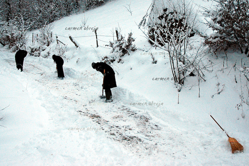 hermitage in winter, nuns clearing the path high in the mountains.