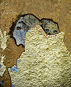 Paint and plaster peeling off a wall the result looks like an abstract artwork woman carrying a baby on her back