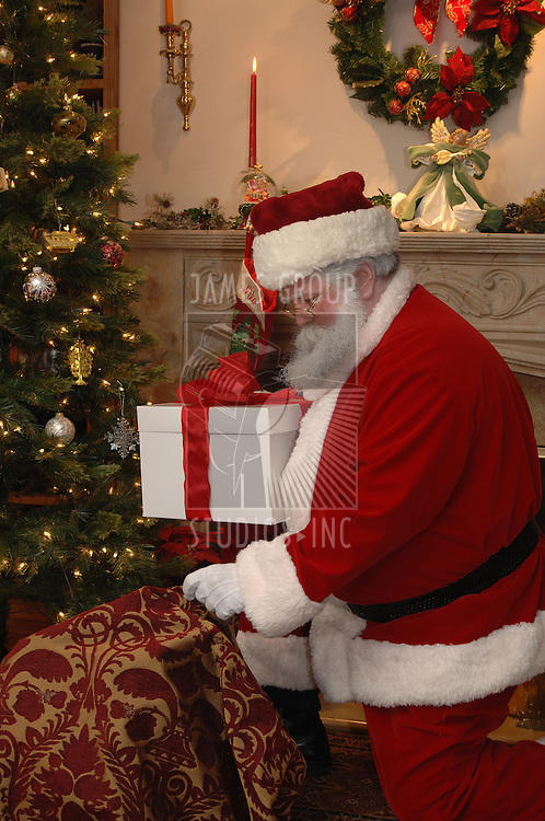 Santa placing a gift under the tree from his sack of toys