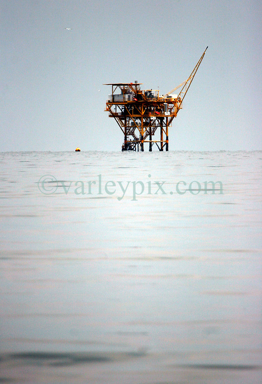 26 May 2010. Barataria Bay, Louisiana. <br /> An oil platform in the Gulf of Mexico just off the coast as seen from Barataria Bay. The environmental and economic impact is devastating with many shrimp boats tied up, vacation rentals and charter boat fishing trips cancelled the only business for shrimpers is loading and laying boom and working for big oil. Oil from the Deepwater Horizon catastrophe is evading booms laid out to stop it thanks in part to the dispersants which means the oil travels at every depth of the Gulf and washes ashore wherever the current carries it. <br /> Photo credit; Charlie Varley<br /> www.varleypix.com