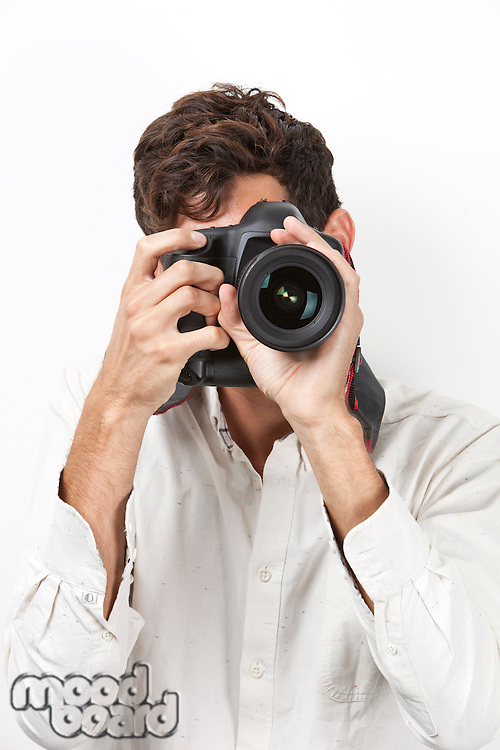 Young man taking photograph with retro style camera against white background