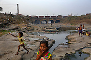 Freight train carrying coal makes way on the bridge as children play at a polluted river near coal waste dumping site in Dhanbad, Jharkhand, India on Dec 5, 2014.<br /> (Photo by Kuni Takahashi)