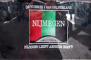 Nederland, Netherlands, Nijmegen, 4-4-2015 Markt in het centrum van Nijmegen. Bij een kraam hangen vlaggen vant NEC. Gisteren werden ze kampioen in de jupiler league en vandaag is de huldiging. Achterkant van een t-shirt waarop de animositeit tussen nijmegen en arnhem uitgedrukt wordt. Nijmegen leeft, arnhem beeftFOTO: FLIP FRANSSEN/ HOLLANDSE HOOGTE