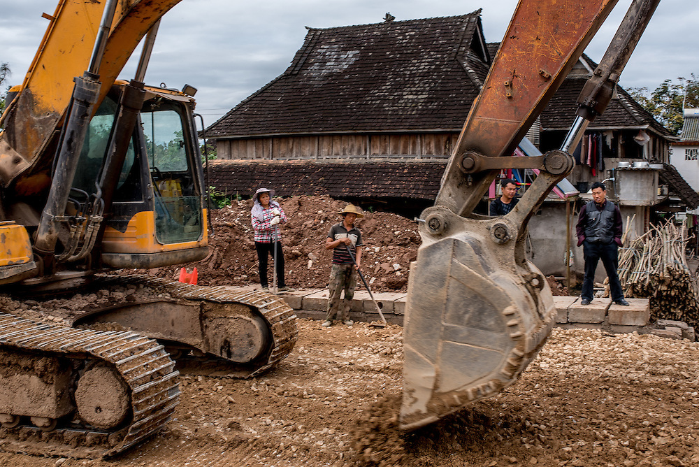 A construction crew builds a new road in Manhenuan village, Xishuangbanna, China. With the financial success of the nearby Dai minority cultural village at Olive Dam, residents of Manhenuan are trying to open their village up to tourism as well.