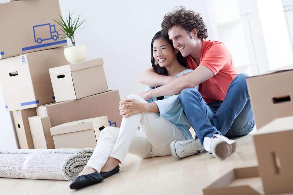 Young multi-ethnic couple resting while moving into their new home.