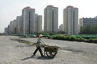 Strassenarbeiter vor einer Wohnsiedlung beim Olympiagelaende. © Urs Bucher/EQ Images