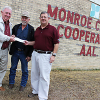 RAY VAN DUSEN/BUY AT PHOTOS.MONROECOUNTYJOURNAL.COM<br /> From left, Cedar Creek Volunteer Fire Department Board of Directors President Buzzy Cullum and Cedar Creek VFD Chief Andy Lee accept a donation from Monroe County Co-Op Manager David Hodges on behalf of the co-op and the Land O'Lakes Foundation.
