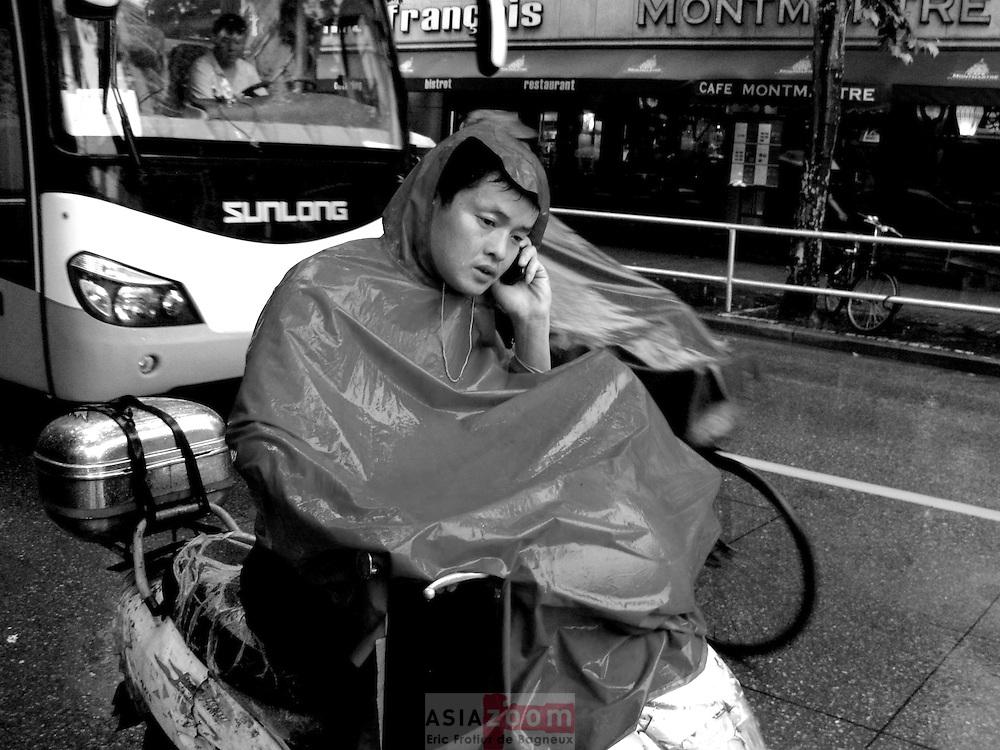 Au telephone malgré la pluie dans la circulation a Shanghai en Chine, juin 2006