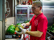 11 DECEMBER 2018 - SINGAPORE:  A vender cuts pineapple in the Haig Road Market and Food Centre in the Geylang neighborhood. The Geylang area of Singapore, between the Central Business District and Changi Airport, was originally coconut plantations and Malay villages. During Singapore's boom the coconut plantations and other farms were pushed out and now the area is a working class community of Malay, Indian and Chinese people. In the 2000s, developers started gentrifying Geylang and new housing estate developments were built.      PHOTO BY JACK KURTZ