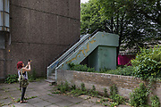 London, England, UK, May 31 2018 - Housing activist and local resident Aysen Dennis takes pictures of a block currently almost empty of Aylesbury Estate,  a housing estate in Walworth, South East London. <br /> Aylesbury  estate, once the largest estate in Europe, is currently undergoing a major regeneration programme by demolishing and replacing of the dwellings with modern houses controlled by a housing association. Some residents and activists including Ms Dennis still protest against the demolition and the gentrification of London.<br /> London is facing a major housing crisis, due to rising cost and under-supply.