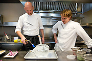 Chef de cuisine Simon Davies and chef Grant Achatz, prepare a dish with Purple Shiso tea, Red Bud flowers, ice fish wafer and miso atop a block of ice at Alinea, an upscale restaurant which underwent a total gut renovation in the Lincoln Park neighborhood of Chicago, Ill., on Thursday, April 28, 2016. Nathan Weber for the New York Times