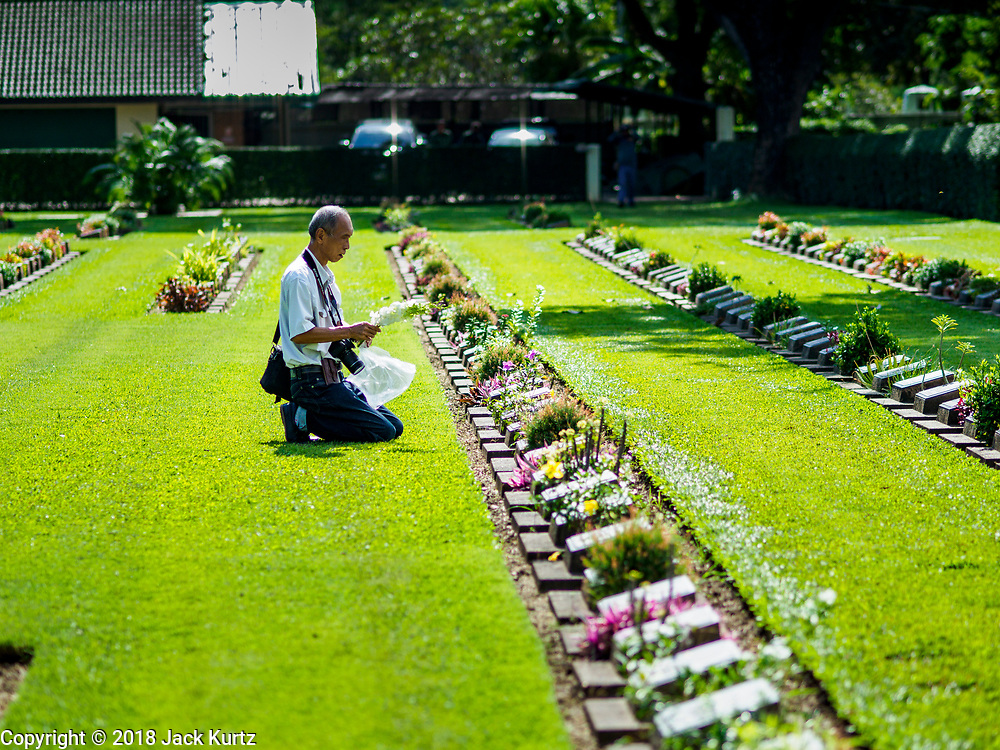 """11 NOVEMBER 2018 - KANCHANABURI, KANCHANABURI, THAILAND: A man leaves flowers on a headstone during the Rememberance Day ceremony at the Kanchanaburi War Cemetery in Kanchanaburi, Thailand. Kanchanaburi is the location of the infamous """"Bridge On the River Kwai"""" and was known for the """"Death Railway"""" built by Japan during World War II using allied, principally British, Australian and Dutch, prisoners of war as slave labor. There are 6,982 people buried in the cemetery, including 5,000 Commonwealth soldiers and 1,800 Dutch soldiers. November 11, 2018 marked the 100th anniversary of the end of World War I, celebrated as Rememberance Day in the UK and the Commonwealth and Veterans' Day in the US.    PHOTO BY JACK KURTZ"""