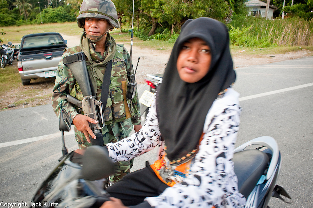 "Sept 26, 2009 -- PATTANI, THAILAND:  A Muslim woman passes a Thai soldier during a Thai army security operation near Krue Se Mosque in Pattani, Thailand, Sept. 26. Thailand's three southern most provinces; Yala, Pattani and Narathiwat are often called ""restive"" and a decades long Muslim insurgency has gained traction recently. Nearly 4,000 people have been killed since 2004. The three southern provinces are under emergency control and there are more than 60,000 Thai military, police and paramilitary militia forces trying to keep the peace battling insurgents who favor car bombs and assassination.   Photo by Jack Kurtz / ZUMA Press"