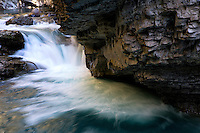Water cut through Johnston Canyon in Banff National Park, Alberta creating a deep gorge with a series of waterfalls and small cascades