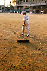 School softball player raking the outfield after game in Tokyo Japan