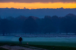 © Licensed to London News Pictures. 05/12/2019. London, UK. A dog walker enjoys the sunrise over a frosty and misty Richmond Park this morning as weather forecasters predict warmer weather for the South East. Photo credit: Alex Lentati/LNP