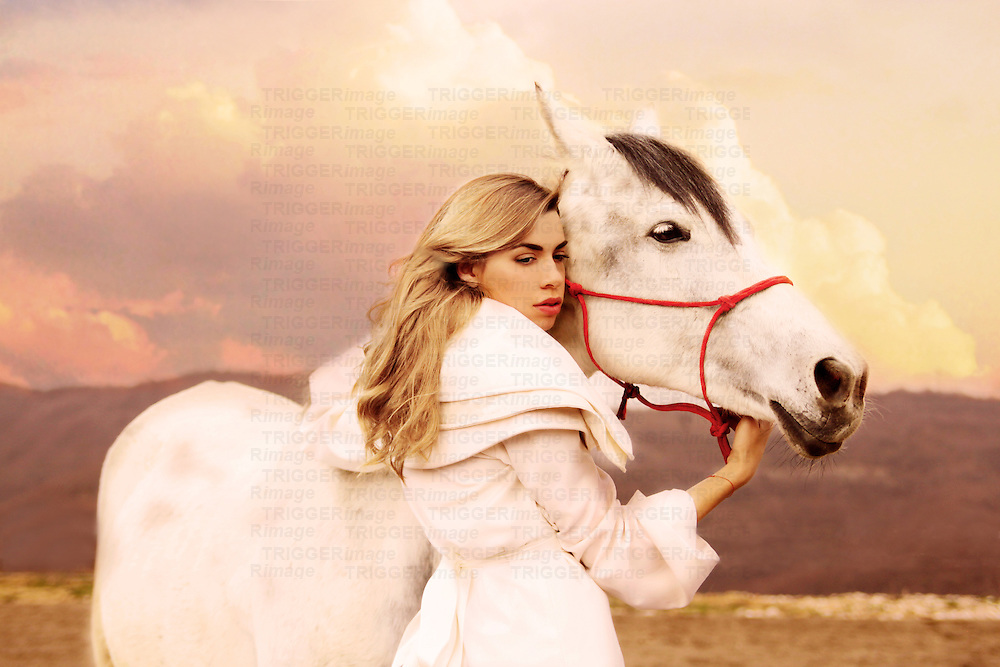 Close-up portrait of female youth dressed in white standing next to a white horse.