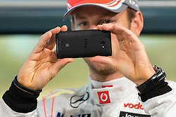 """© London News Pictures. 31/01/2013 . Woking, UK.  Jenson Button using his mobile phone to photograph photographers and the media. Team McLaren Mercedes drivers Jenson Button and Sergio """"Checo"""" Perez unveil the new MP4-28 Formula 1 car at the McLaren Technology Centre in Woking, Surrey, UK on  Thursday, Jan. 31, 2013. Photo credit : Ben Cawthra/LNP"""