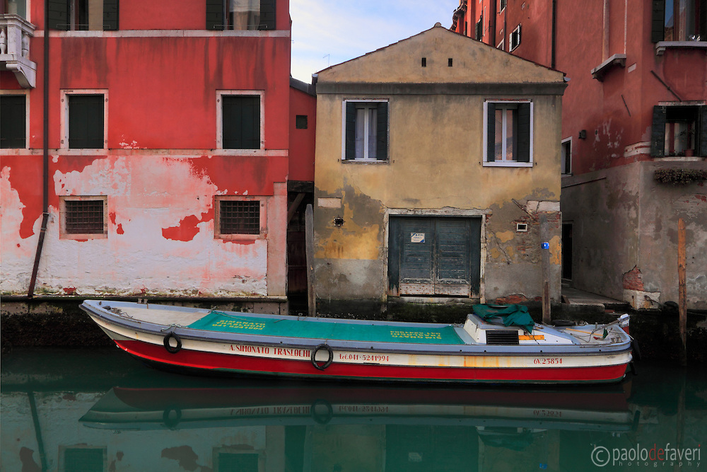 A small scene at a canal in Venice, a removals firm's boat and typical Venetian houses.