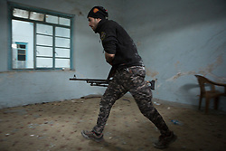 Licensed to London News Pictures. 01/04/2017. Mosul, Iraq. A Federal Police machine gunner runs across a West Mosul room after firing at Islamic State militants in Iraq today (01/04/2017). Iraqi forces continue to fight house to house as they push further into West Mosul. Iraqi forces are now advancing on the city's old districts where Islamic State fighters still hold out. Photo credit: Matt Cetti-Roberts/LNP