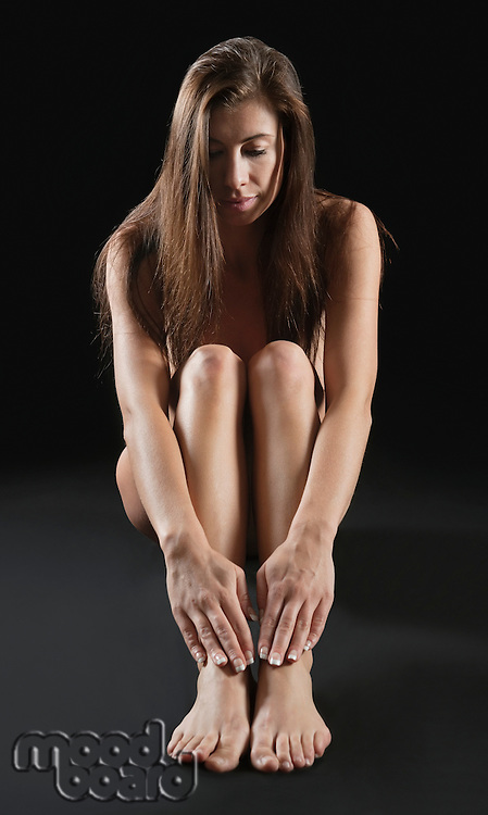 Beautiful young naked woman sitting over black background