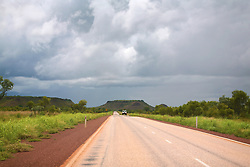 A lonely vehicle travels the road between Fitzroy Crossing and the Broome Highway in the Kimberley wet season.  Traffic is light at this time of year and frequent storms fill the creeks.
