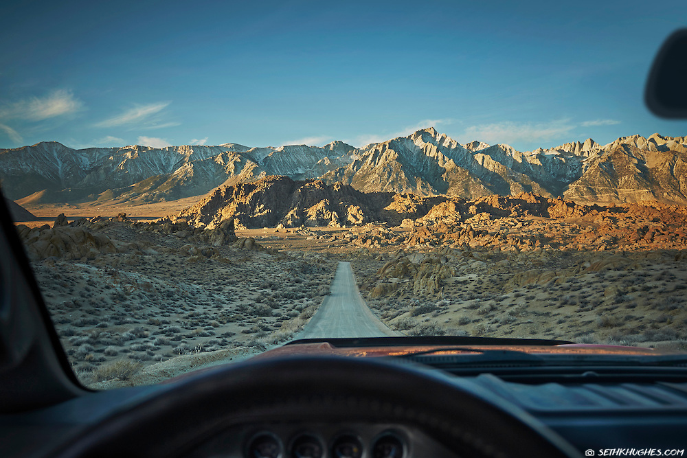 Point of view (POV) from behind the steering wheel looking down a dirt road at the Sierra Nevada Mountains of California.