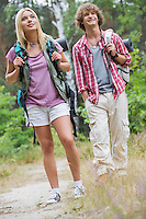 Couple looking away while hiking in forest