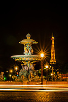 "One of the two monumental fountains at Place de la Concorde. This one is called ""Fountain of the RIvers."" The illuminated Eiffel Tower is the background, Paris, France."