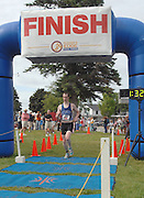 Anthony Smucler of Mt. Pleasant, Michigan crosses the finish line to win the mens overall title at the inaugural Little Traverse Triathalon in Harbor Springs, Michigan.