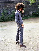 Profile of young man with an Afro hairstyle standing alone.