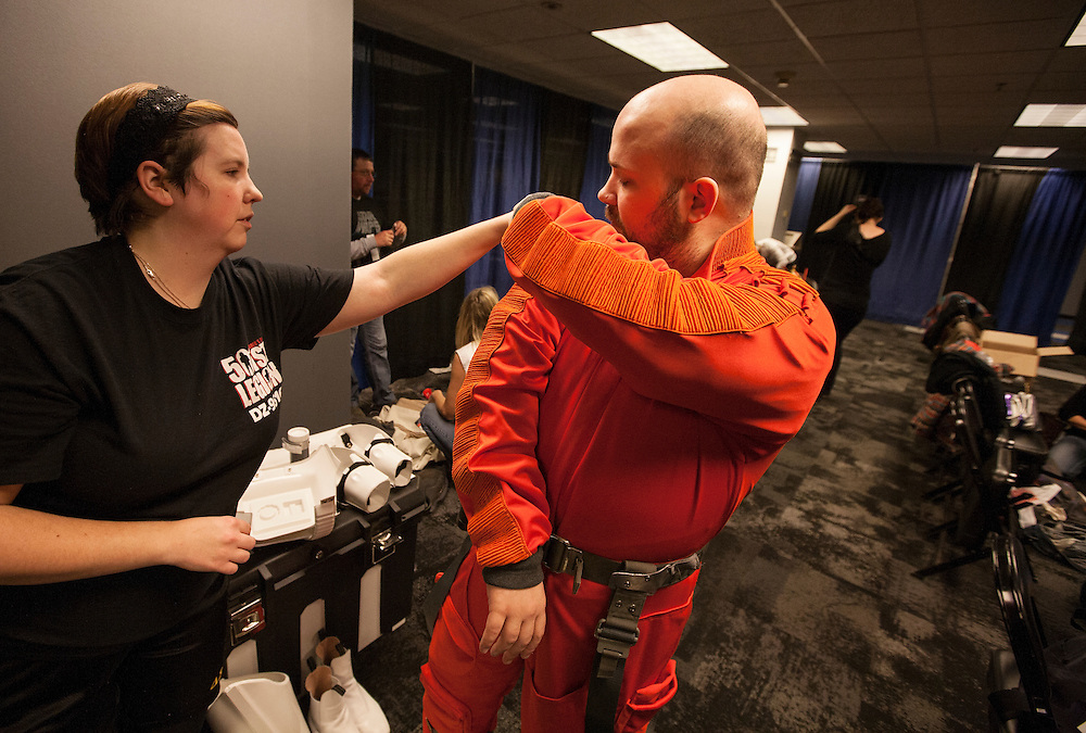 Amanda Fineran, left, of Bloomington helps X-Wing pilot Bowie Sessions of Shakopee trim frayed threads from his costume before Star Wars night at the Timberwolves game at Target Center in Minneapolis December 15, 2015.