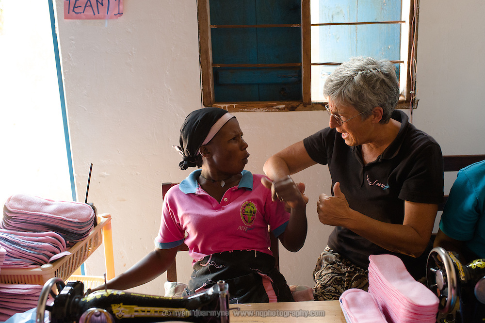 Dorothy Maynard, a volunteer (at right), with Annette Namale at the Afripads factory in the village of Kitengeesa in the Central Region of Uganda on 30 July 2014.<br /> <br /> Started by volunteers in 2009, Afripads manufactures reusable fibre sanitary pads made locally by community residents. Beginning with a single employee, the company now employs roughly 100 women and produces approximately 700 kits (consisting of pads, holders and a bag) each week. At USh 12,000 to 15,0000 (&pound;2.75 to &pound;3.40) for a kit that lasts approximately one year, Afripads offer a significant saving over disposables which may cost in excess of USh 42,000 (&pound;9.60) over the course of a year. And for the many girls and women who cannot afford disposables, they offer an affordable and more hygienic alternative to rags, cotton wool or toilet paper, all of which are frequently used. At schools where Afripads have been distributed, teachers report that absenteeism has dropped sharply as girls who previously did not have access to proper sanitary pads now no longer stay home when they have their periods.