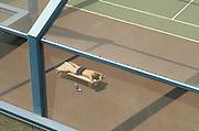 man sunbathing on a tennis court