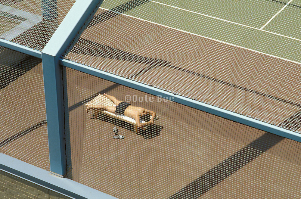 man sunbathing on a tennis court