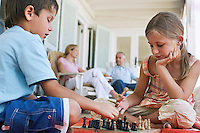 Brother and sister (7-9) playing chess on porch parents in background