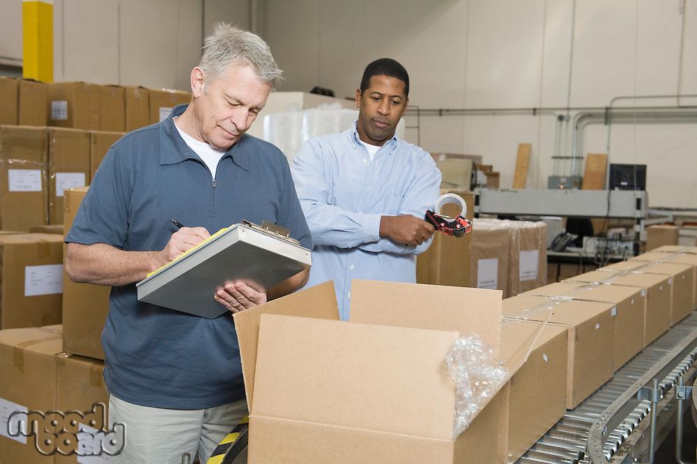 Men inspecting goods in distribution warehouse