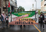 Protesters march through the streets of Montreal holding a banner to encourage people boycotting the junket companies that continue to do business with Israel