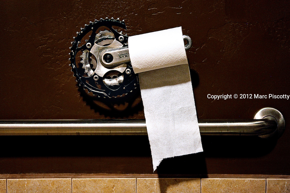 SHOT 4/28/12 8:53:47 PM - A used crank arm and chain rings serve as an improvised toilet paper holder in the men's restroom at Hot Tomato Cafe and Pizzeria in Fruita, Colorado during the Fruita Fat Tire Festival. The City of Fruita is located in the western part of Mesa County, Colorado, in the United States. Economically, it started out as a fruit producing region, but today it is well known for its outdoor sports such as mountain biking, hiking, and rafting. The area surrounding Fruita is renowned for its mountain biking trails, most notably including the North Fruita Desert/18 Road trail system. (Photo by Marc Piscotty / © 2012)