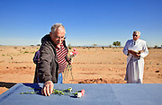 "18 MARCH 2010 - SURPRISE, AZ: Tom Lanphear (CQ) from Phoenix, places flowers and dirt in the shape of a cross on the caskets during burials in White Tanks Cemetery on Camelback Rd. in an unincorporated part of the county near Surprise. The county spent about $2.5 million to inter indigent people in what is Maricopa County's ""potters field."" About 3,000 people, children and adults, are buried in the dusty field west of Phoenix.     PHOTO BY JACK KURTZ"
