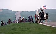 Covered wagons and horseback riders on the modern South Dakota prairie outside Rapid City, South Dakota.
