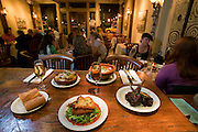 Zuzu Restaurant, Napa, California. Napa Valley. Zuzu serves tapas: small plates of food to accompany a drink. On the bar, with two glasses of sherry, (foreground, clockwise) sizzling prawns, smokey Spanis Pimenton, garlic and thyme; queso frito: pan fried Manchego cheese with roasted poblano chiles; roasted spaghetti squash with apple cider syrup and midnight moon cheese; leblebi: garbanzo bean soup, roasted peppers, poached eggs and harissa; Moroccan barbecue glazed lamb chops.